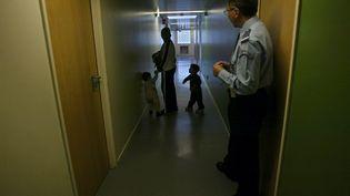 Un policier regarde une jeune femme et ses deux enfants, le 27 octobre 2003, dans un couloir du centre de rétention de la zone d'attente de l'aéroport de Roissy-Charles de Gaulle (JOEL ROBINE / AFP)
