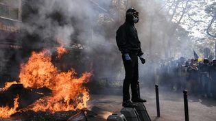 Un activistehabillé en noirmanifeste à Paris, le 1er mai 2019. (ANNE-CHRISTINE POUJOULAT / AFP)