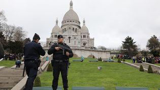 Des policiers patrouillent à proximité de la basilique du Sacré Coeur à Paris, le 30 mars 2018. (LUDOVIC MARIN / AFP)