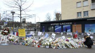 Une femme dépose une bougie devant l'Hyper Cacher, porte de Vincennes (Paris), le 16 janvier 2016, plus d'un an après l'attentat terroriste perpétré dans l'épicerie. (BERTRAND GUAY / AFP)