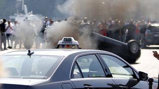 Une voiture dépendant du service Uber a été retournée par des taxis en colère, à Paris, le 25 juin 2015. ( CHARLES PLATIAU / REUTERS)
