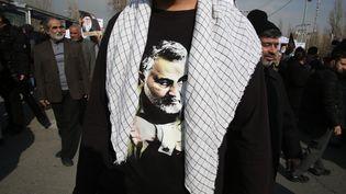 Un Iranien porte un tee-shirt présentant le visage de Qassem Soleimani, le 3 janvier 2020 à Téhéran. Ce général iranien a été tué quelques heures plus tôt à Bagdad (Irak) par une frappe américaine. (ATTA KENARE / AFP)