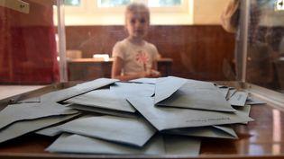 Un enfant derrière une urne dans un bureau de vote d'Authon, dans le Nord de la France. (GUILLAUME SOUVANT / AFP)