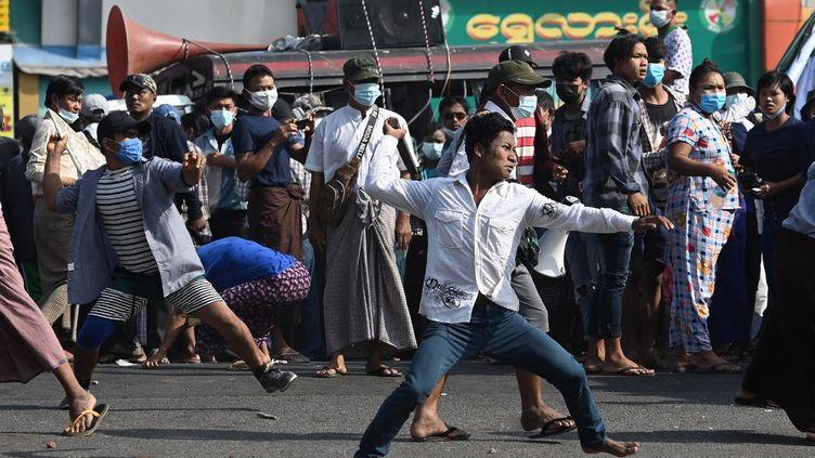 Des soutiens de la junte militaire lancent des projectiles à l'encontre d'habitants, le 25 février 2021 à Rangoun. (SAI AUNG MAIN / AFP)