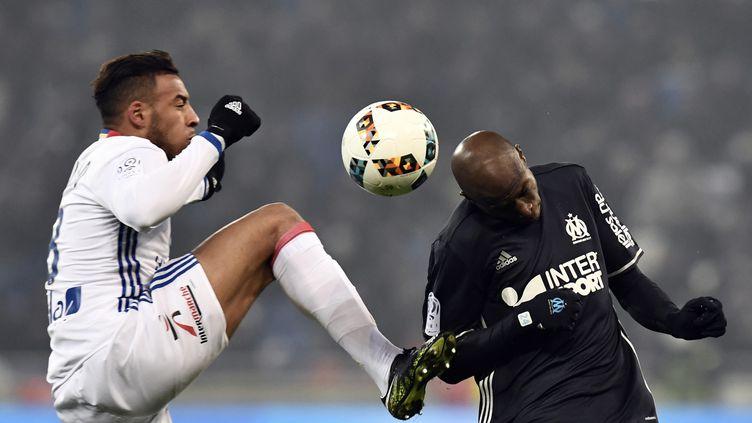 Corentin Tolisso (Lyon) et Rod Fanni (Marseille) se battent pour récupérer le ballon (JEFF PACHOUD / AFP)