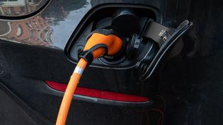 Une voiture électrique en charge à Paris, le 25 novembre 2020. (RICCARDO MILANI / HANS LUCAS / AFP)