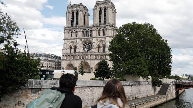 Deux touristes ont les yeux rivés sur Notre-Dame de Paris. (ZAKARIA ABDELKAFI / AFP)