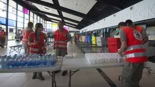Des membres de la Croix-Rouge préparent des boissons pour les familles évacuées de Saint-Martin, le 9 septembre 2017, à l'aéroport de Pointe-à-Pitre, en Guadeloupe. (HELENE VALENZUELA / AFP)