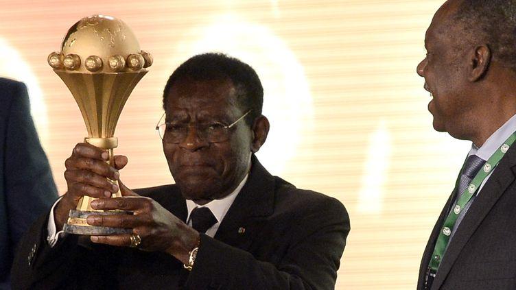 Le président équato-guinéen Teodoro Obiang brandit la Coupe d'Afrique des nations, lors du tirage au sort, le 3 décembre 2014. (STEPHANE DE SAKUTIN / AFP)