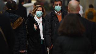 Un homme et une femme portent des masques dans les rues de Milan, en Italie, dimanche 23 février 2020. (ANDREA DIODATO / NURPHOTO / AFP)