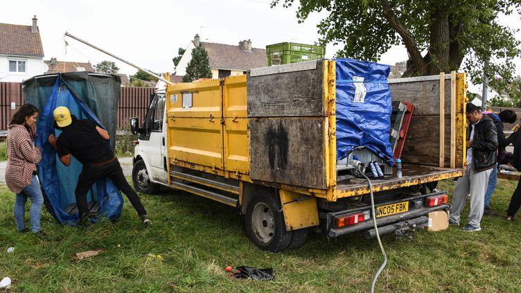 Des bénévoles de l'association L'Auberge des migrants installent une douche mobile pour des migrants, le 5 septembre à Calais. (DENIS CHARLET / AFP)