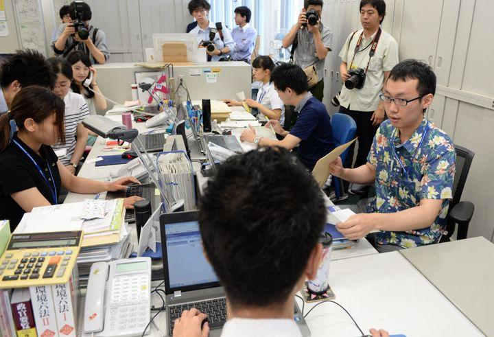 """Des employés du ministère de l'Environnement japonais posent devant les photographes en chemisettes et polos pour le lancement de la campagne """"Super Cool Biz"""", le 1er juin 2015 à Tokyo. (MASAHIRO SUGIMOTO / YOMIURI / AFP)"""