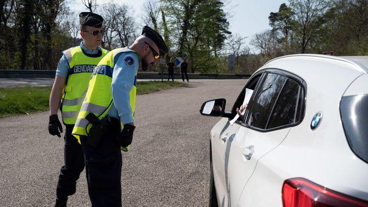 Des gendarmes contrôlent les papiers d'un automobiliste, le 10 avril 2020, sur une route de Saverne (Bas-Rhin). (DAVID BETZINGER / HANS LUCAS)
