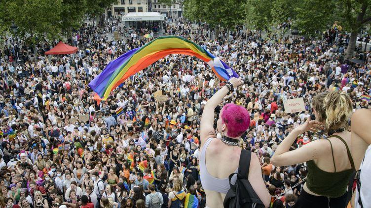 Deux personnes brandissent un drapeau arc-en-ciel lors de la Marche des fiertés de Paris le 26 juin 2021. (JACOPO LANDI / HANS LUCAS / AFP)