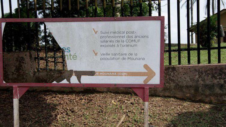 Un panneau indicateur cassé montre la direction de l'Observatoire de la santé de Mounana (OMS) créé par le groupe français Areva au Gabon. Censé«suivre l'état des travailleurs (de sa filiale gabonaise,la Compagnie des mines d'uranium de Franceville-Comuf),et les indemniser», il est fermé depuis 2015.    (AMAURY HAUCHARD / AFP)