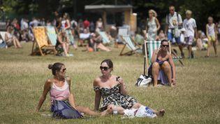 Des Britanniques se reposent dans un parc de Londres, le 16 juillet 2013, alors que l'Angleterre est touchée par sa première canicule depuis 2006. ( MAXPPP)
