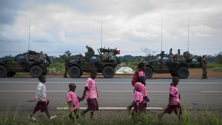 Des enfants marchent le long d'une route camerounaise, alors que les troupes françaises se positionnent près de la frontière avec la Centrafrique, le 5 décembre 2013. (FRED DUFOUR / AFP)