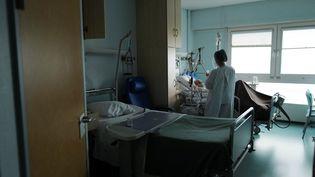 Une soignante s'occupe d'un patient atteint du Covid-19 à l'hôpital Emile Muller à Mulhouse, le 16 février 2021. Photo d'illustration. (SEBASTIEN BOZON / AFP)
