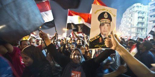 Des Egyptiens manifestent leur joie le 3 juillet 2013 place Tahrir au Caire après la déposition par l'armée du président islamiste Mohamed Morsi. Les manifestants brandissent notamment un portrait du nouvel homme fort du pays, Abdel Fattah al-Sissi. (AFP - Khaled Desouki)