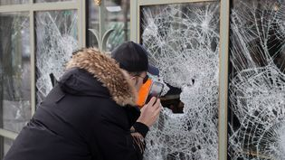Un homme prend des photos des dégâts,au lendemain des manifestations sur les Champs-Elysées, à Paris. (GEOFFROY VAN DER HASSELT / AFP)