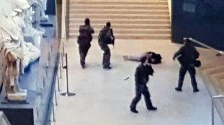 L'assaillant du Carrousel du Louvre, au sol, est entouré par quatre militaires, le 3 février 2017, à Paris. (ALEXANDRE MARCHI / MAXPPP)