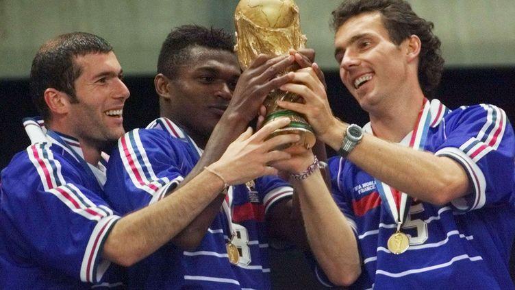 Zinedine Zidane, Marcel Desailly et Laurent Blanc soulèvent la Coupe du monde de football, le 12 juillet 1998, après la victoire de la France contre le Brésil au Stade de France. (MICHEL EULER / AP / SIPA)