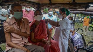 Une soignante vaccine des patients àSiliguri (Inde), le 28 juillet 2021. (DIPTENDU DUTTA / AFP)