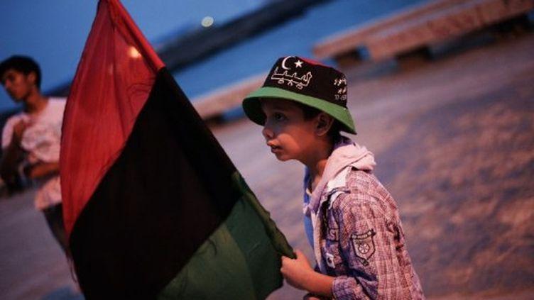 Un enfant libyen tenant une drapeau libyen sur une plage, à Benghazi, le 2 juin 2011 (AFP/Gianluigi GUERCIA)