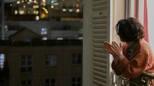 Une femme applaudit les soignants depuis sa fenêtre, à Montreuil (Seine-Saint-Denis),le 21 mars 2020. (REMI DECOSTER / HANS LUCAS / AFP)