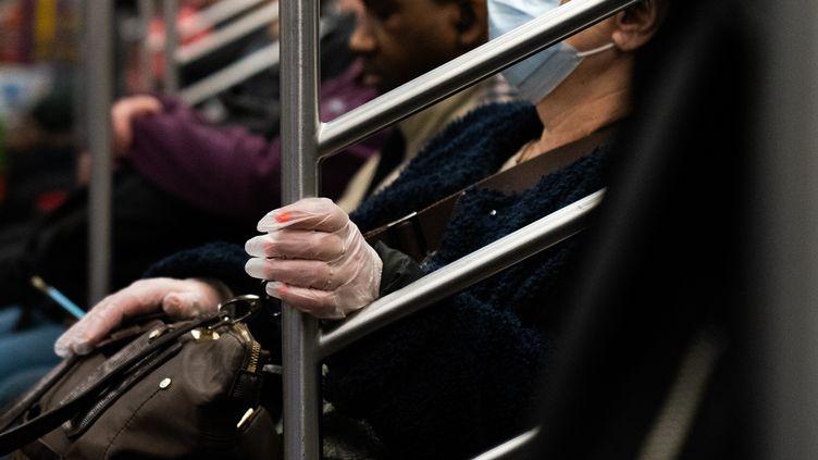 Une femme porte des gants et un masque pour se protéger des germes dans le métro de New York (Etats-Unis), le 9 mars 2020. (JEENAH MOON / GETTY IMAGES NORTH AMERICA / AFP)