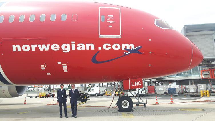 Le commandant de bord de Norwegian, Philippe Duforest, et le tout nouveau chef de base de Norwegian à Paris,Joost Smits,posentdevant un appareil de la compagnie low-cost en mai 2017 à l'aéroport Chales de Gaulle. (ISABELLE RAYMOND / FRANCEINFO)