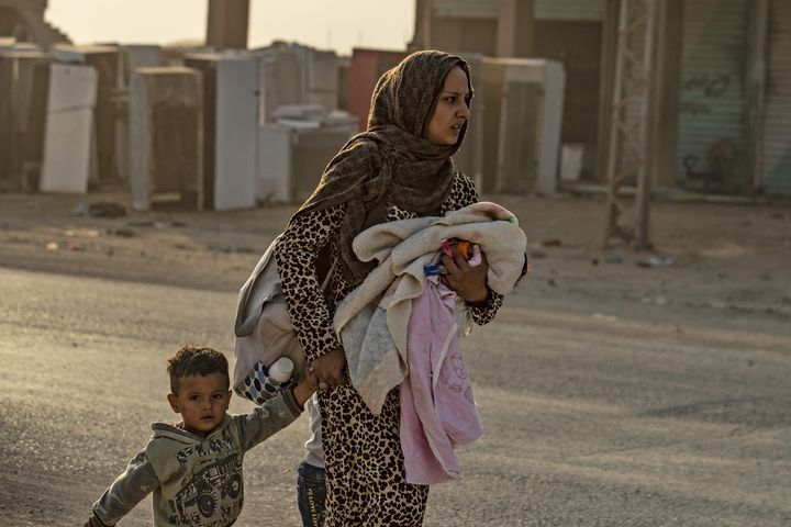 Une femme kurde et son fils fuient le village de Ras al-Aïn, le 9 octobre 2019, alors que les premières frappes turques commencent. (DELIL SOULEIMAN / AFP)