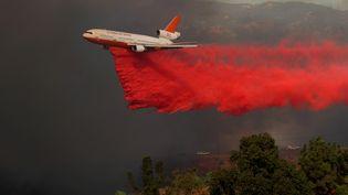 Un avion lance des produits destinés à ralentir le feu, le 9 octobre 2017. (MIKE BLAKE / REUTERS)