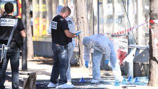 Des policiers inspectent un Abribus percuté par un homme qui a été interpellé, lundi 21 août 2017 à Marseille. (BORIS HORVAT / AFP)