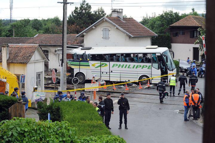 Un bustransportant des enfantsen sortie scolaire est percuté parun train régional, sur un passage à niveau d'Allinges (Haute-Savoie), le 2 juin 2008. (JEAN-PIERRE CLATOT / AFP)