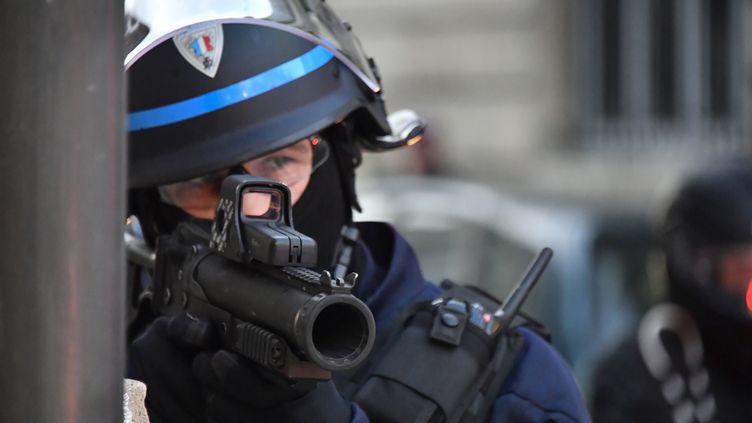 """Un policier tenant un lanceur de balles de défense (LBD40), lors d'une manifestation des """"gilets jaunes"""" à Bordeaux (Gironde), le 2 février 2019. (GEORGES GOBET / AFP)"""