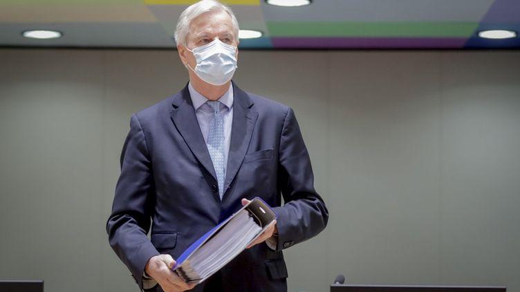 Le négociateur européen Michel Barnier tient dans ses mains l'accord entre le gouvernement britannique et la Commission européenne, au Conseil européen, à Bruxelles, le 25 décembre 2020. (OLIVIER HOSLET / AFP)
