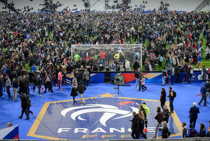 La pelouse du Stade de France envahie par des spectateurs, le 13 novembre 2015. (THOMAS EISENHUTH / DPA / AFP)