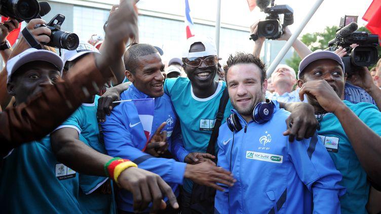 Florent Malouda et Mathieu Valbuena (en blouson bleu), entourés de supporters de l'équipe de France à leur arrivée à Donestk, en Ukraine, le 6 juin 2012. (FRANCK FIFE / AFP)