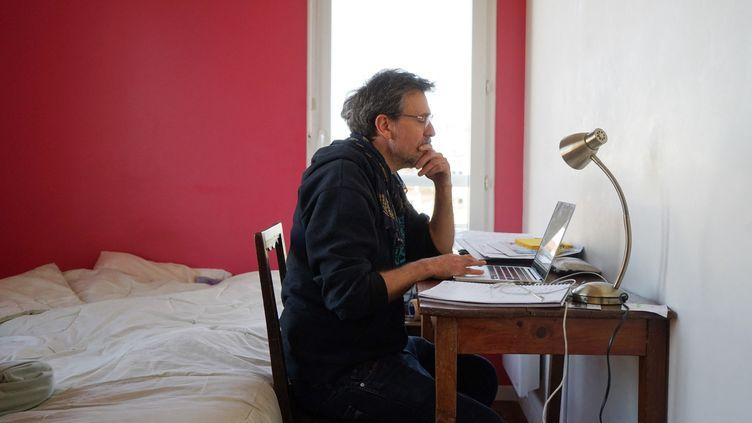Un homme télétravaille depuis sa chambre à Paris, le 8 avril 2021. (MYRIAM TIRLER / HANS LUCAS)