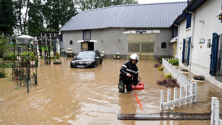 Un pompier intervient dans une rue inondée d'Adé, près de Lourdes (Hautes-Pyrénées), le 3 juin. (LAURENT DARD / AFP)
