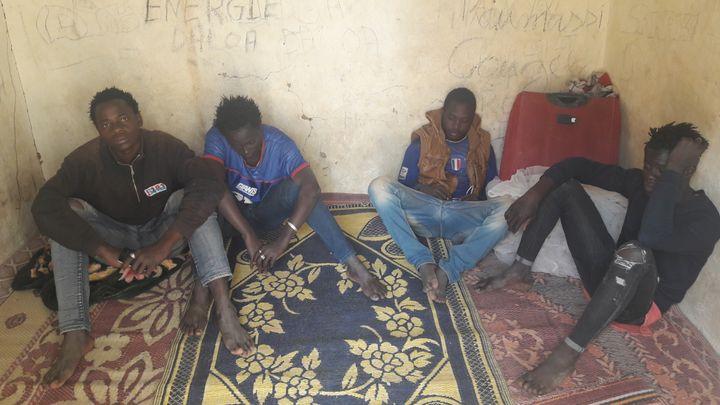 A gauche, assis sur le sol, Koffi Arnaud, 18 ans, originaire de Côte d'Ivoire, déterminé à gagner la Libye au péril de sa vie pour jouer au football en Allemagne, son rêve. (SANDRINE ETOA-ANDEGUE / RADIO FRANCE)