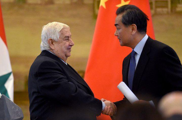 Le ministre syrien des Affaires étrangères, Walid Muallem, sert la main de son homologue chinois, Wang Yi, lors d'une conférence de presse le 24 décembre 2015 à Pékin. (WANG ZHAO / AFP)