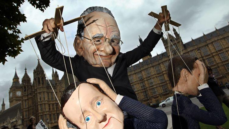 Un manifestant déguisé en Rupert Murdoch manipule une marionnette du Premier ministre britannique, David Cameron. (ADRIAN DENNIS / AFP)