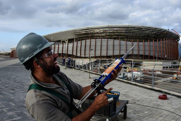 Un ouvrier pose avec son pistolet à mastic devant le parc olympique de Rio de Janeiro (Brésil), le 6 octobre 2015. (CHRISTOPHE SIMON / AFP)