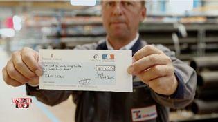 Alexandre de Cuniac, directeur général de Leduc, avec son chèque du trésor public pour le CICE. L'Angle éco, septembre 2015. ( CAPTURE ECRAN FRANCE 2)
