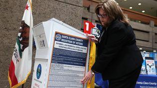 Une électrice dépose un vote dans une boîte prévue pour recevoir les courriers des américains qui optent pour le vote anticipé, à San José, en Californie, mardi 13 octobre 2020. (JUSTIN SULLIVAN / GETTY IMAGES NORTH AMERICA / AFP)