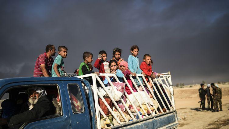 Des Irakiens déplacés arrivent dans un camp de réfugiés le 22 octobre 2016 dans la ville de Qayyarah, au sud de Mossoul, alors qu'une opération de récupération de la ville de Mossoul du groupe de l'Etat islamique a lieu. (BULENT KILIC / AFP)