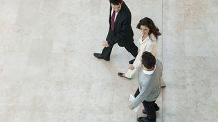 Une femme et deux hommes marchent et parlent ensemble. (MAXPPP)