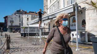 Une femme porte un masque dans le quartierdu Vieux-Port de La Rochelle (Charente-Maritime), le 30 mai 2020. (XAVIER LEOTY / MAXPPP)